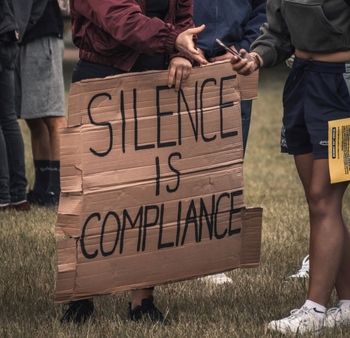 """Protest sign that reads, """"silence is compliance"""""""