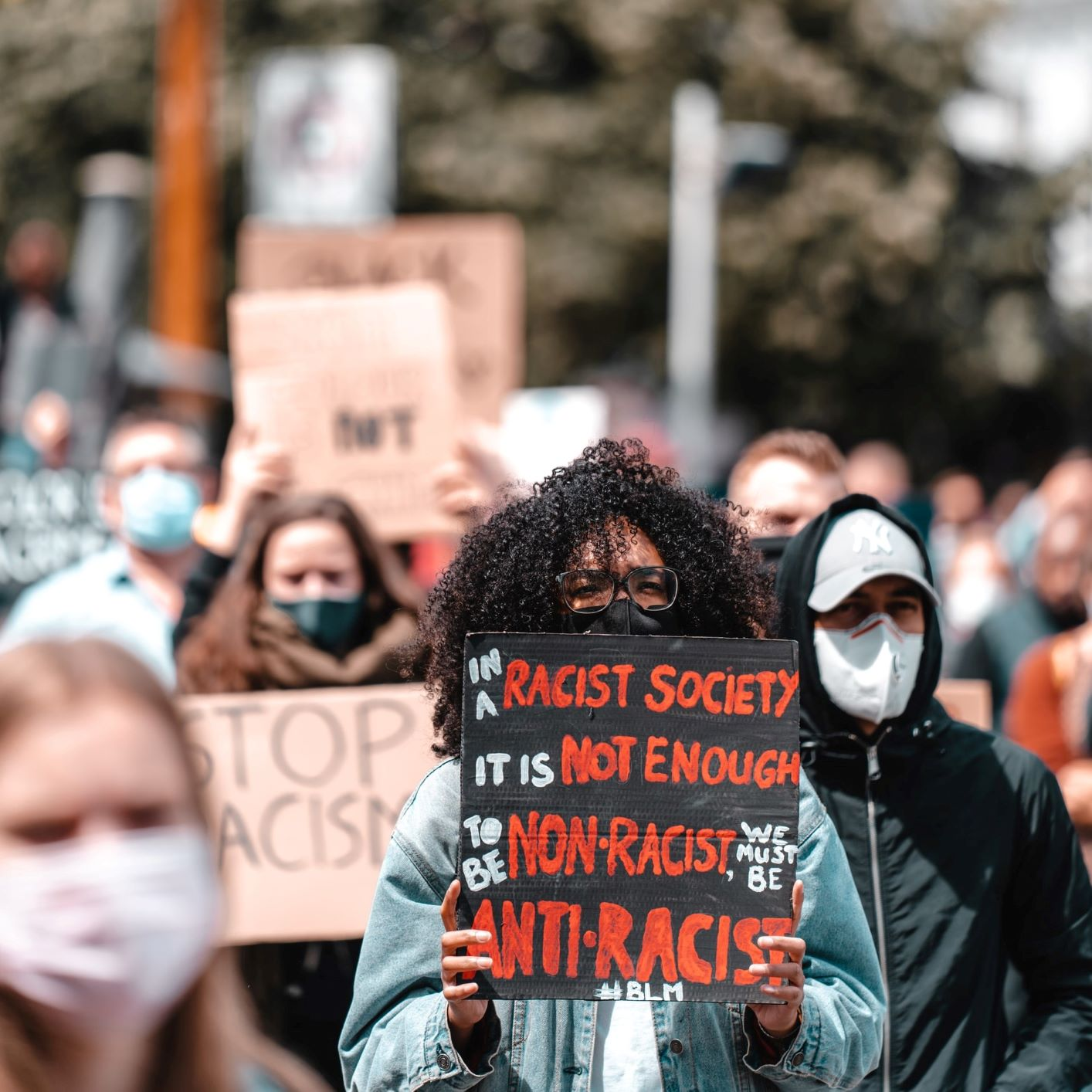 """Black woman marching with protestors with a sign that reads, """"in a racist society it is not enough to be non-racist, we must be anti-racist #BLM"""""""